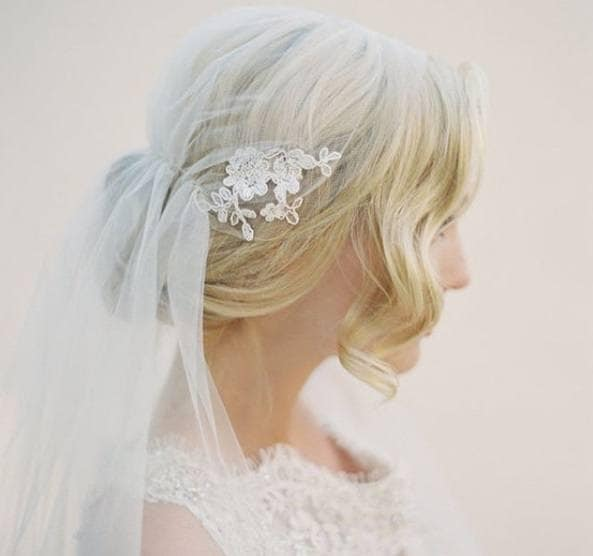 Wedding updos for long hair: Side shot of a bride with long golden blonde hair styled into a wavy vintage updo, complete with a veil, wearing white and posing