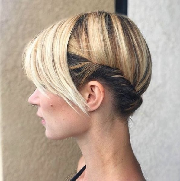 side profile of a blonde with a twisted updo and a long angular fringe