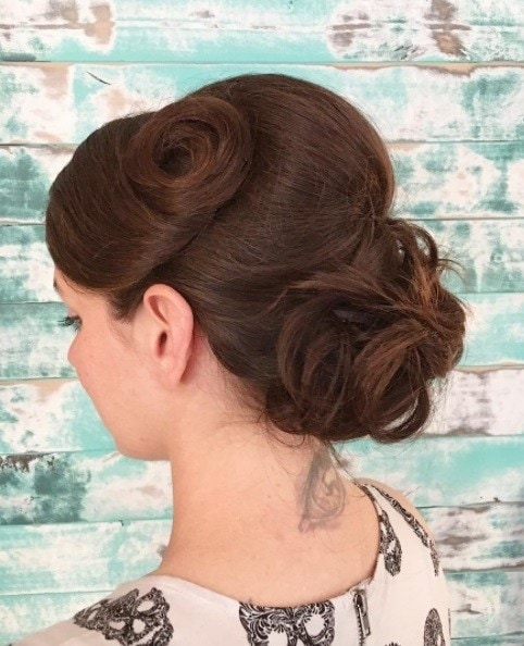 Bridal updos for long hair: Close up shot of a woman with long medium brown hair styled into vintage-inspired curled updo hairstyle.
