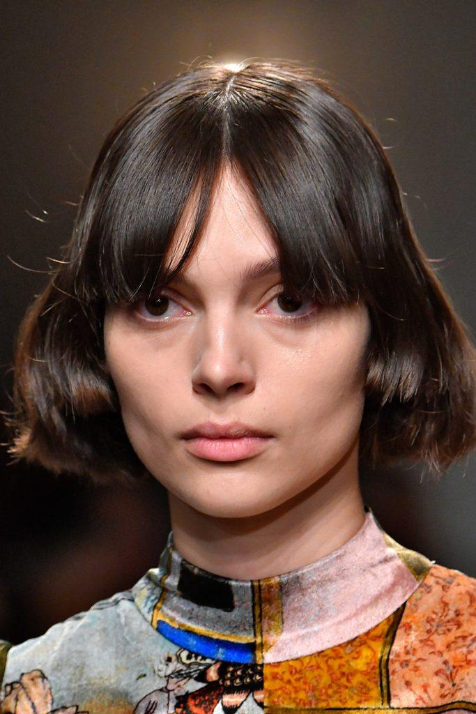 60s hairstyles: brunette model with a mod bob hairstyle on runway