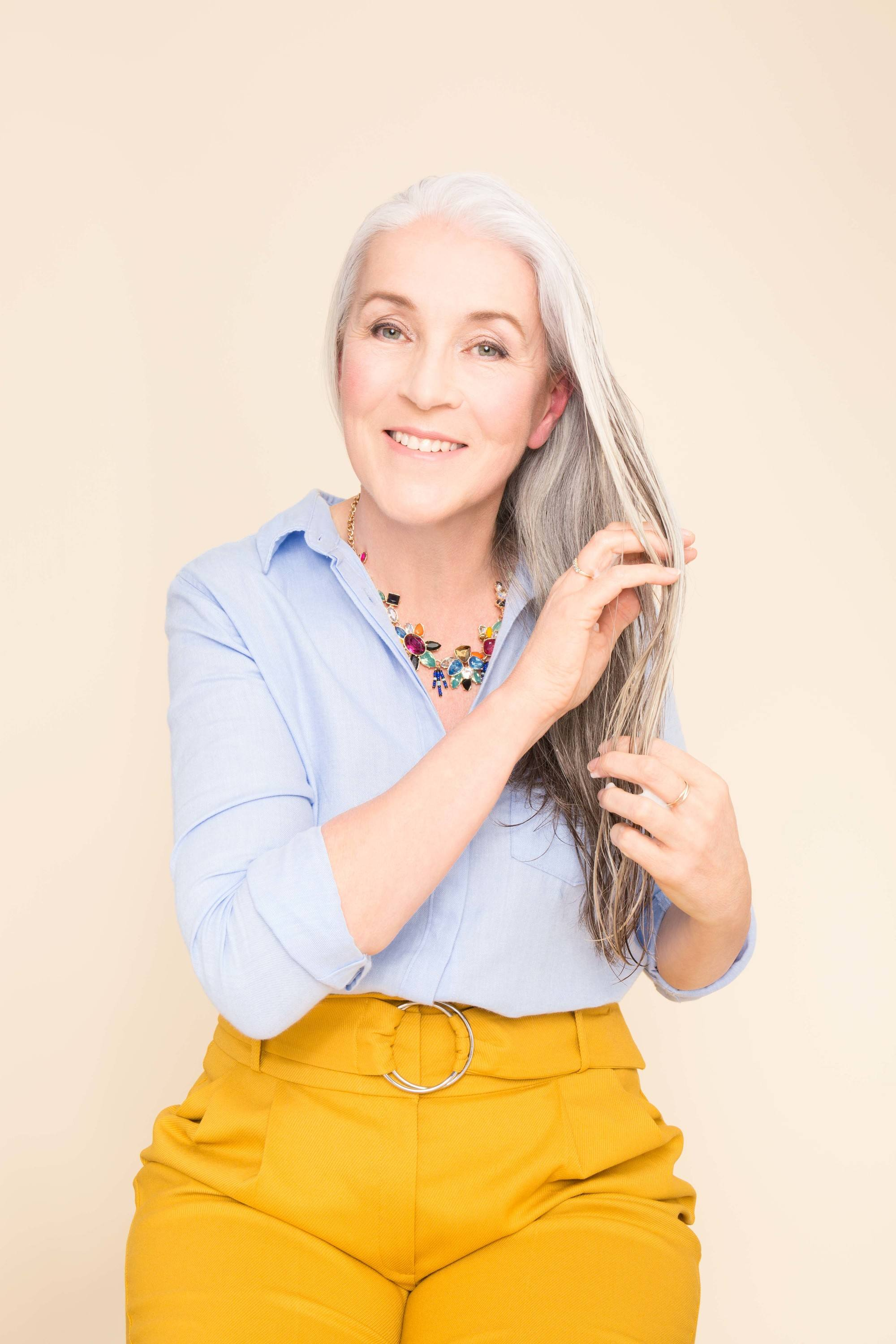 Shampoo full guide: Mature model touching her grey white medium length hair wearing a blue shirt and yellow trousers.