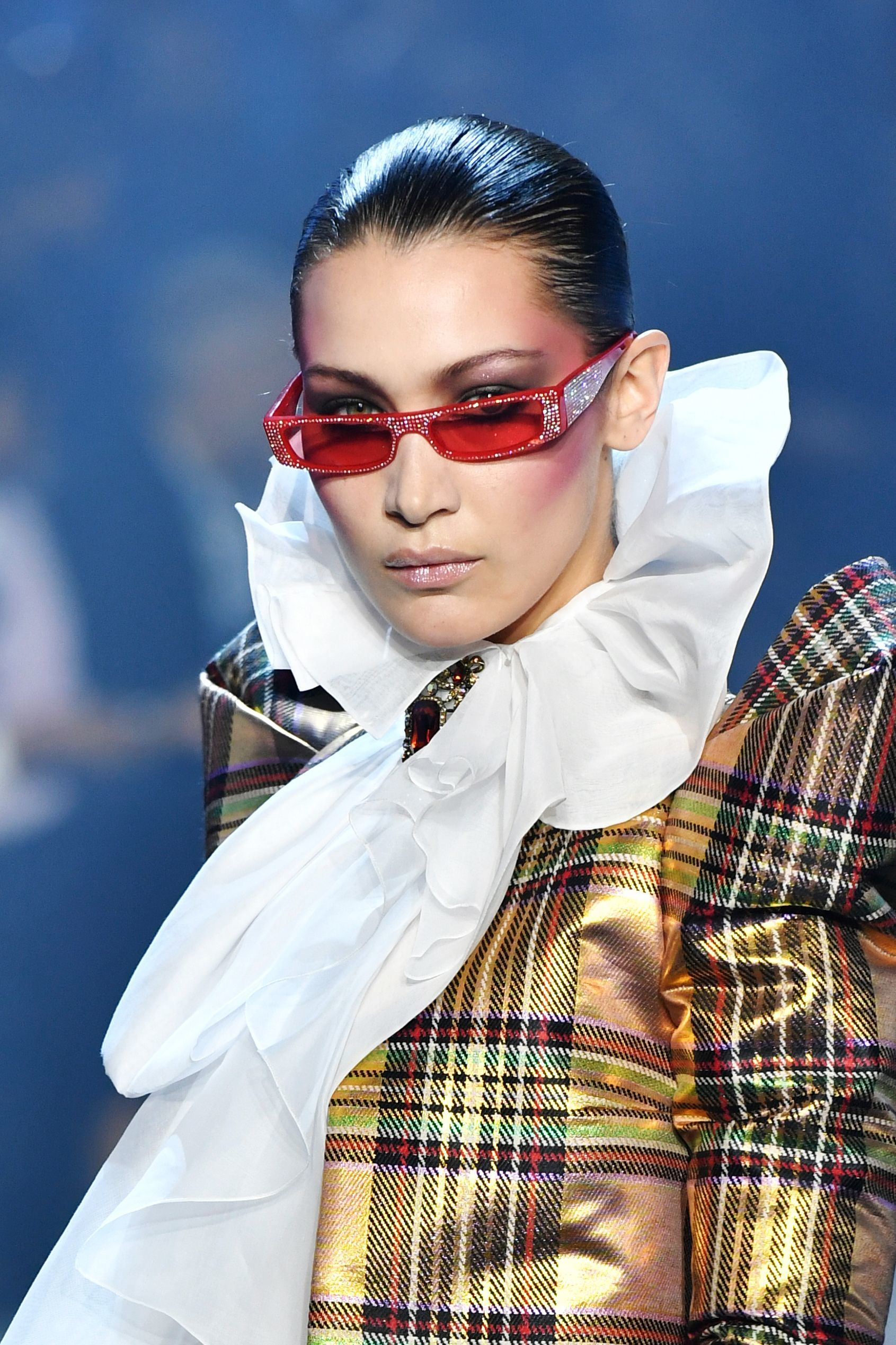 close up shot of bella hadid with micro sunglasses and slicked back hairstyle, wearing neck collar and checked shirt