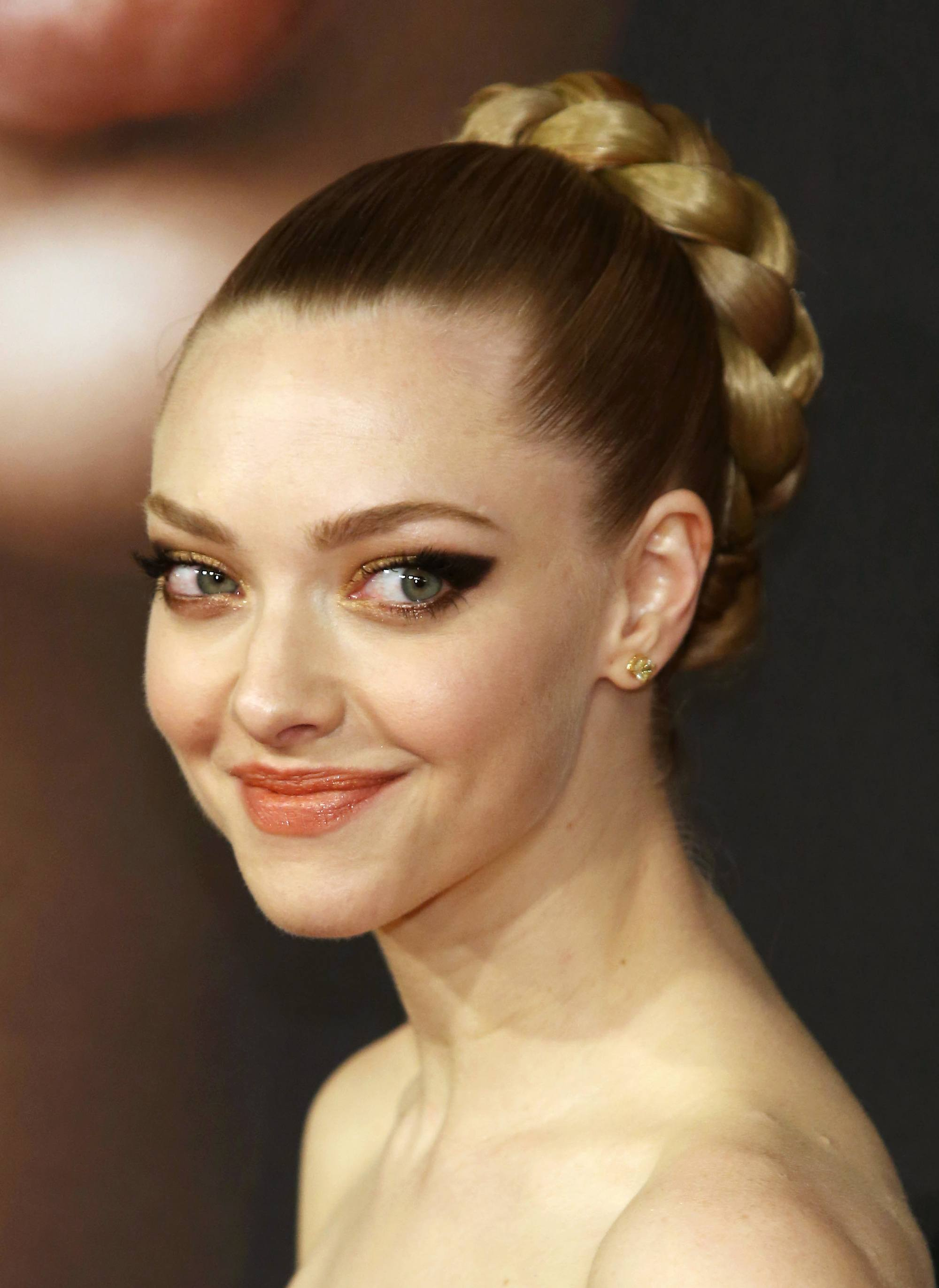 actress amanda seyfried with her hair in a slicked back braided bun
