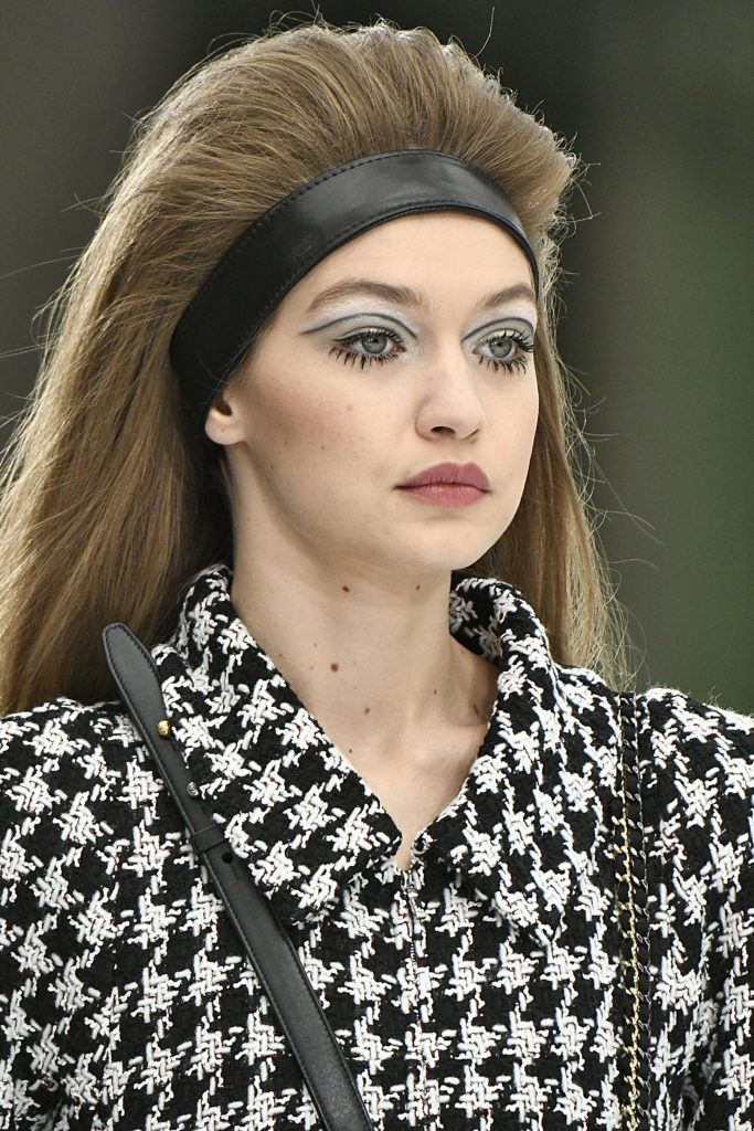 60s hairstyles: model gigi hadid on the catwalk in a houndstooth jacket with backcombed 60s hair and a headband