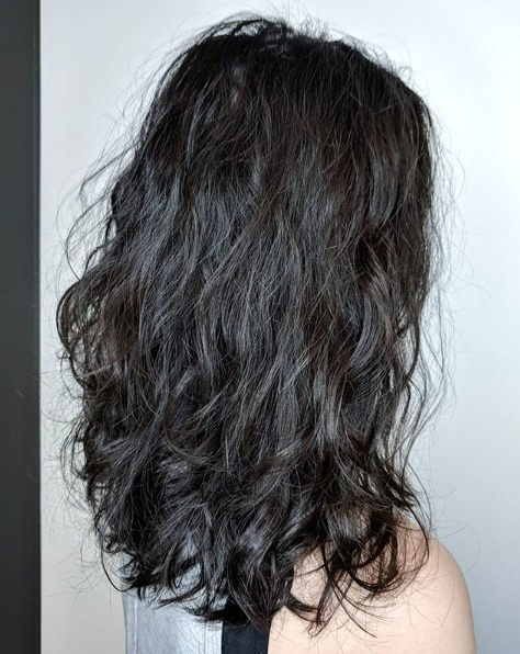 Woman with shoulder length dark brown wavy permed hair.
