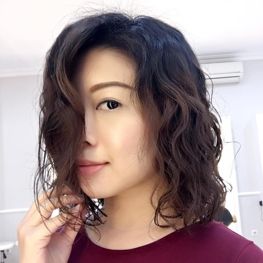 Selfie of an Asian woman with lob length hair in a wavy perm wearing a burgundy top.