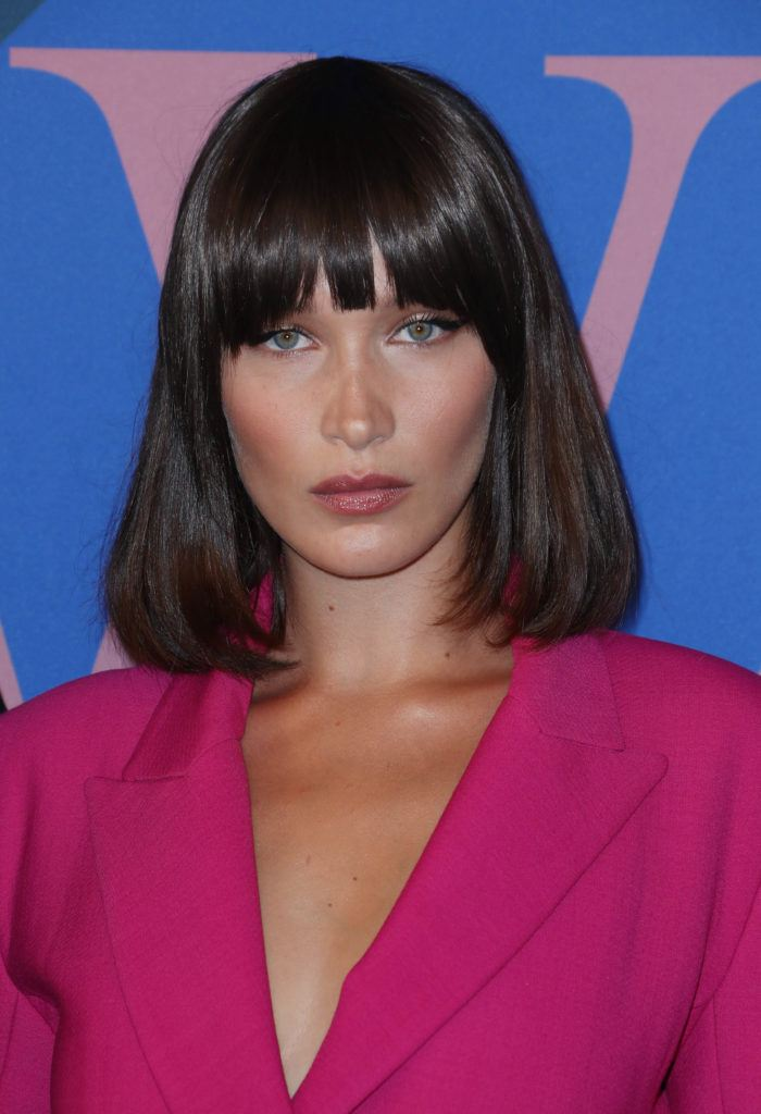 Bella Hadid, with dark brown hair in curled under bob and full bangs