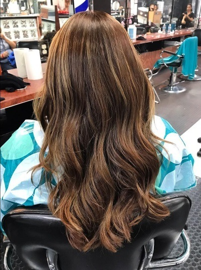 Brunette woman in a salon chair with long wavy permed hair.