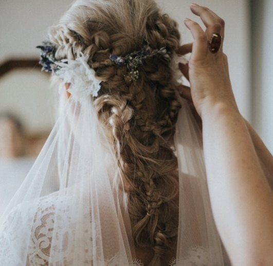 back view of a brunette bride with her hair in an intricate boho braid with a veil