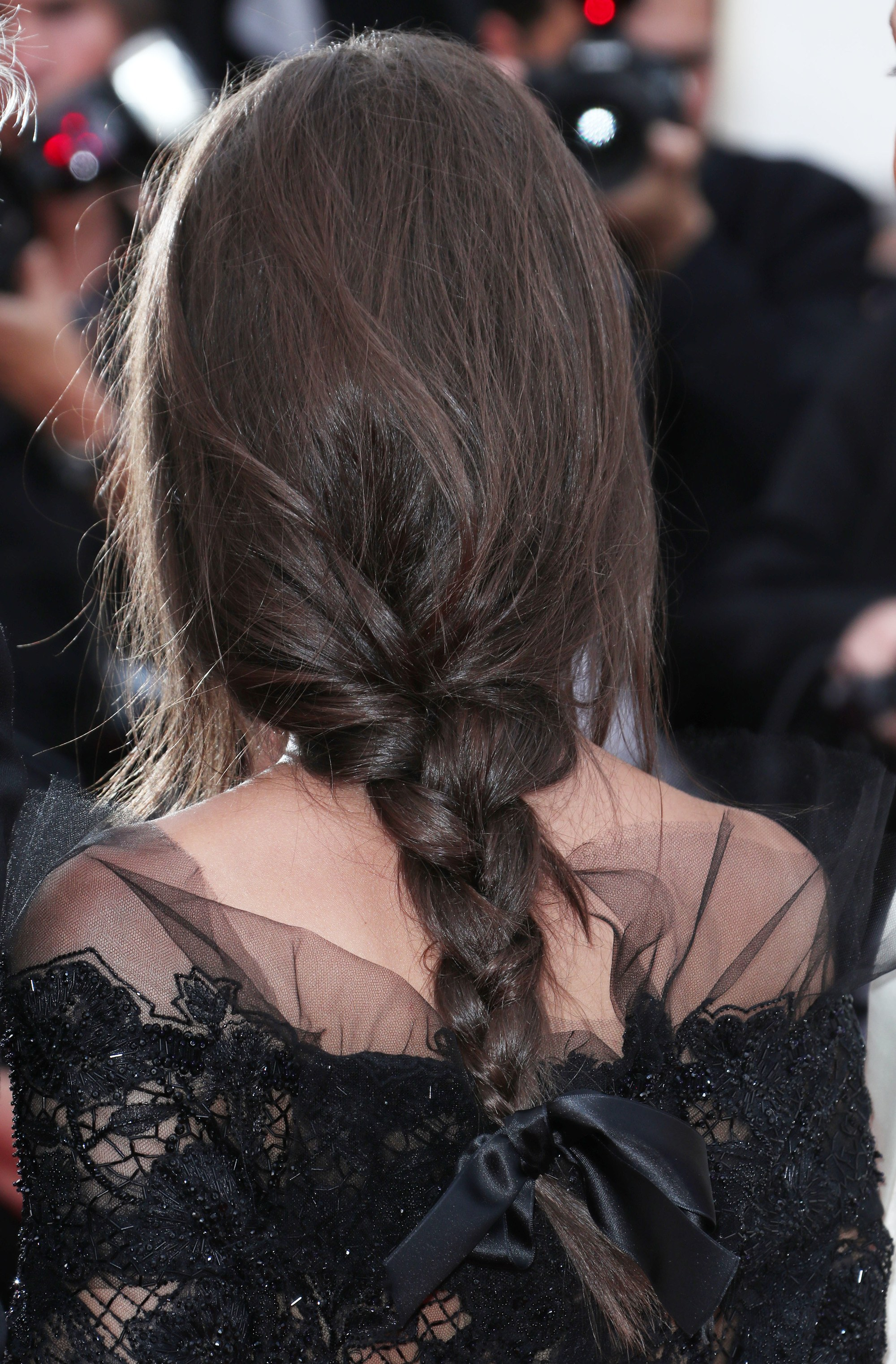 brunette with her hair in a braid with a black ribbon hair tie