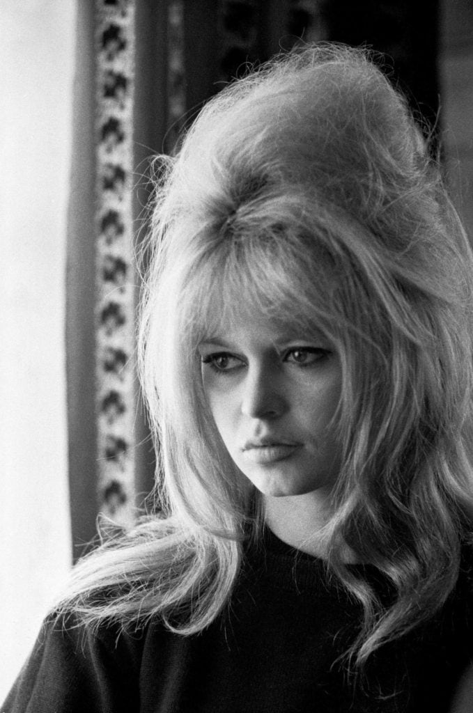 60s hairstyles: Brigitte Bardot light blonde medium length hair styled in a backcombed beehive with soft bardot bangs in black and white photo