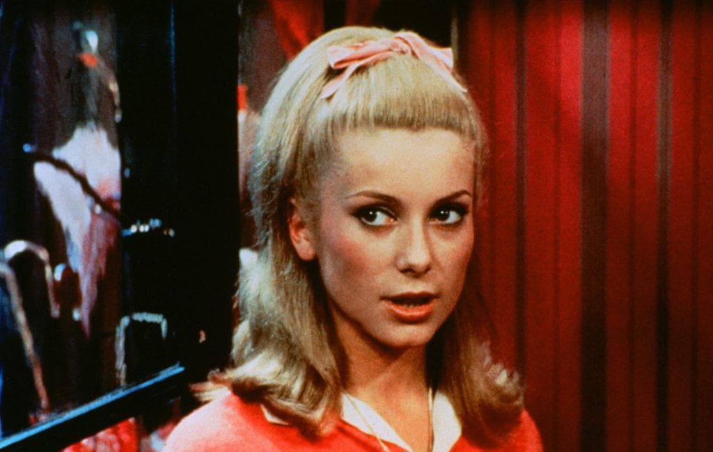 60s hairstyles: Catherine Deneuve shoulder length blonde straight hair with flicked out ends styled in a half up ponytail worn with a pink ribbon bow