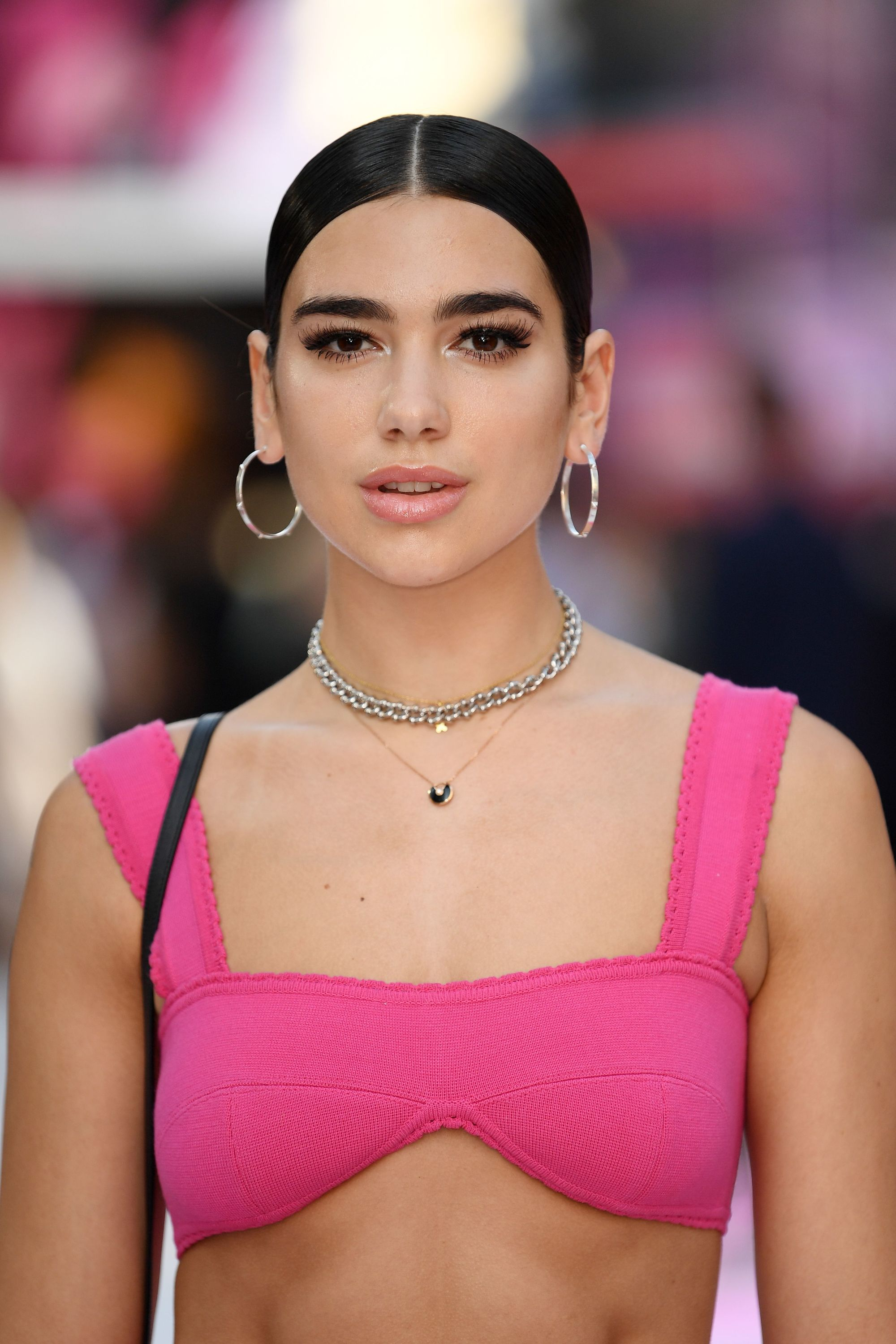 singer dua lipa with her dark hair in a slick centre parting