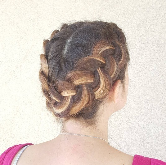 woman with blond and brunette highlighted hair in a double dutch braid updo