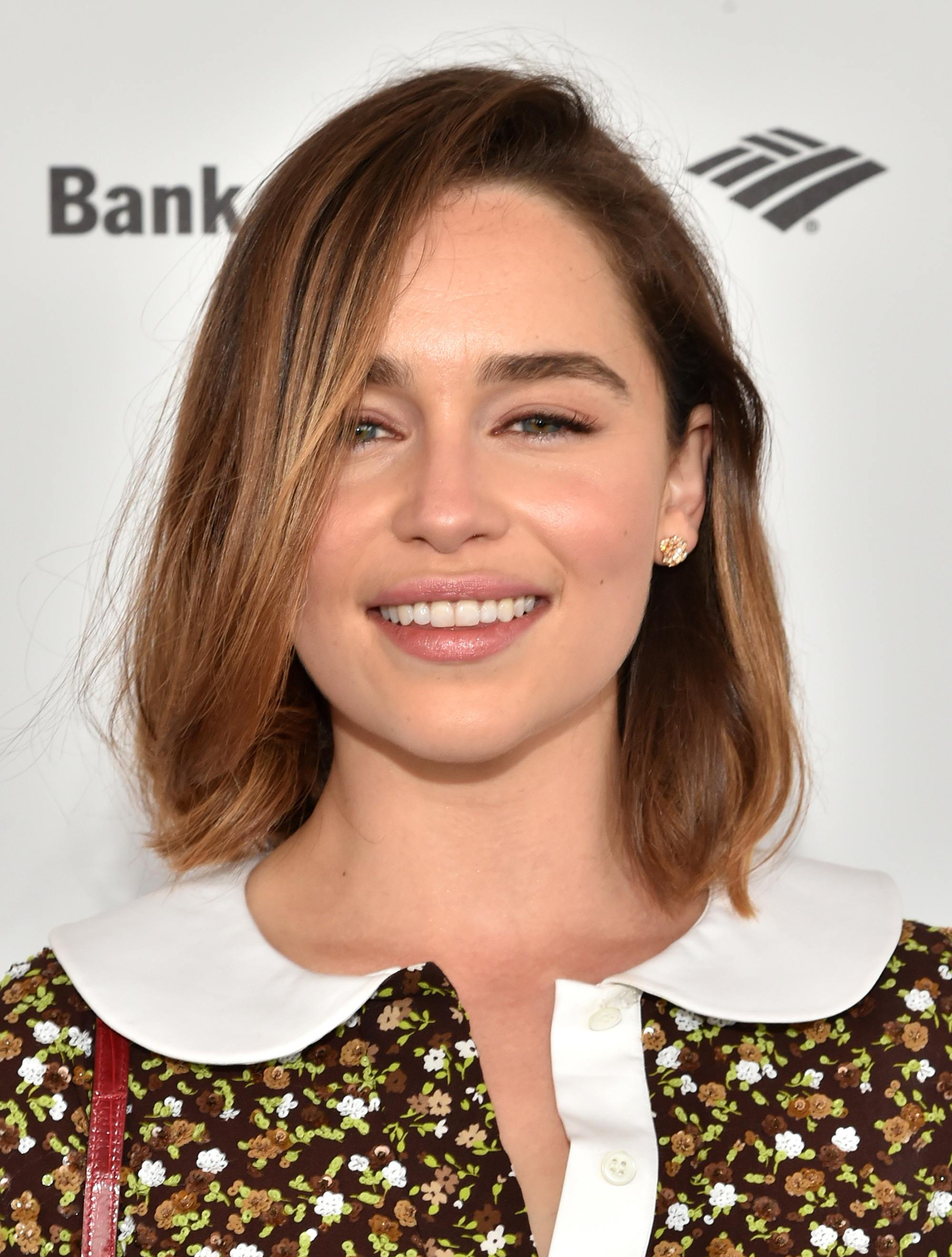 Shoulder length layered hair: Emilia Clarke with brunette mid-length light brown balayage hair worn in a side parting