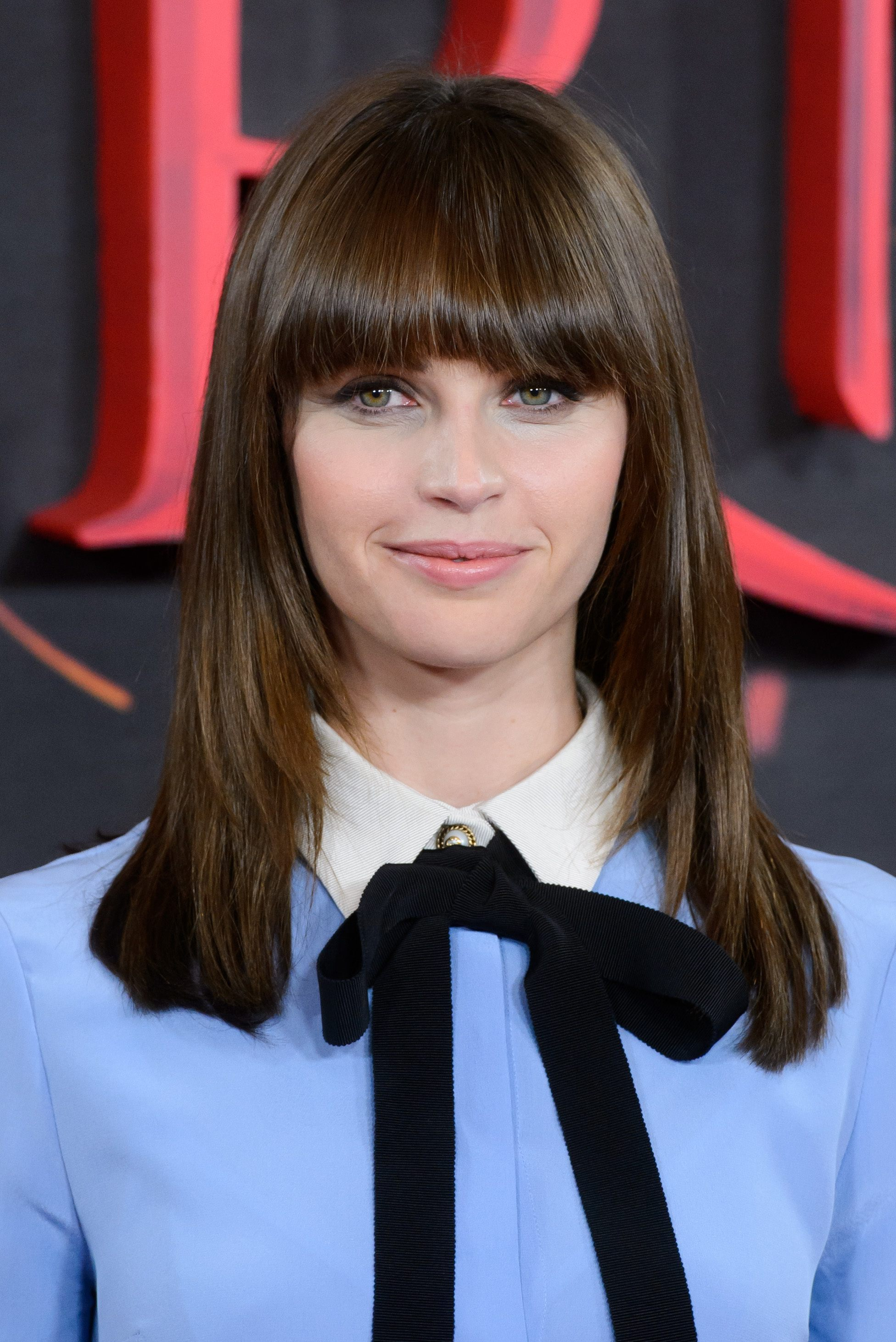 Shoulder length layered hair: british actress felicity jones with shoulder length brunette hair with bangs and layers