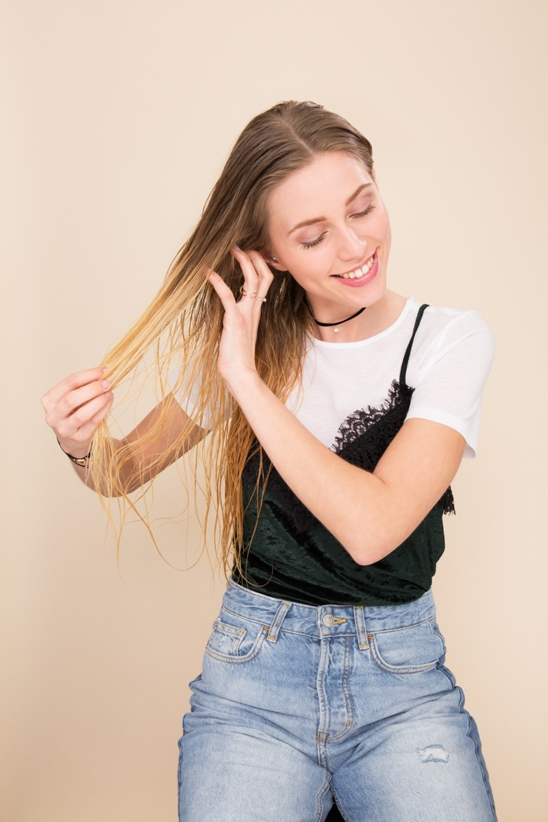 Shampoo full guide: Woman finger combing her straight long blonde hair wearing a t-shirt ad cami with jeans.