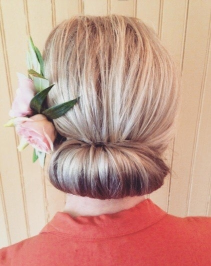 blonde woman with her hair in a gibson tuck updo hairstyle with a pink rose accessory