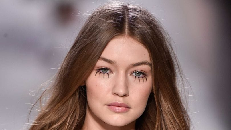 model gigi hadid on the runway with her signature long wavy hair