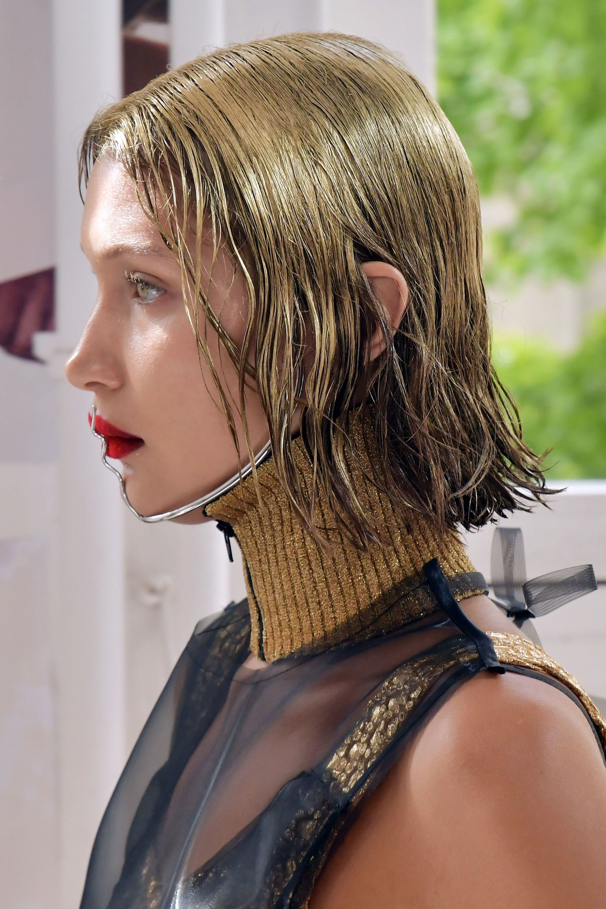 Bella hadid on the Maison Margiela runway with spray painted golden hair with red lips and black outfit