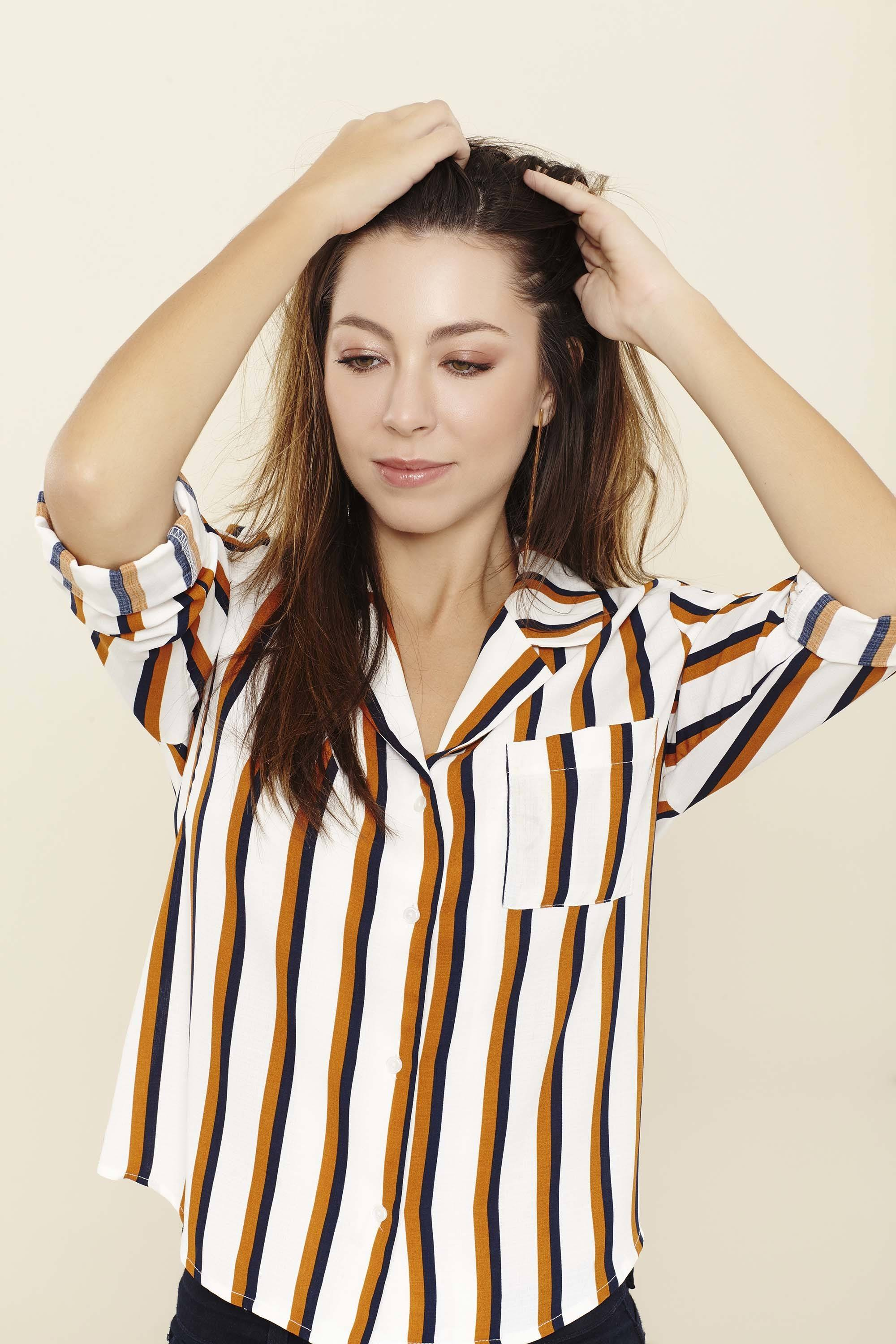 Shampoo full guide: Woman touching her long brown straight hair wearing a brown and white striped shirt.
