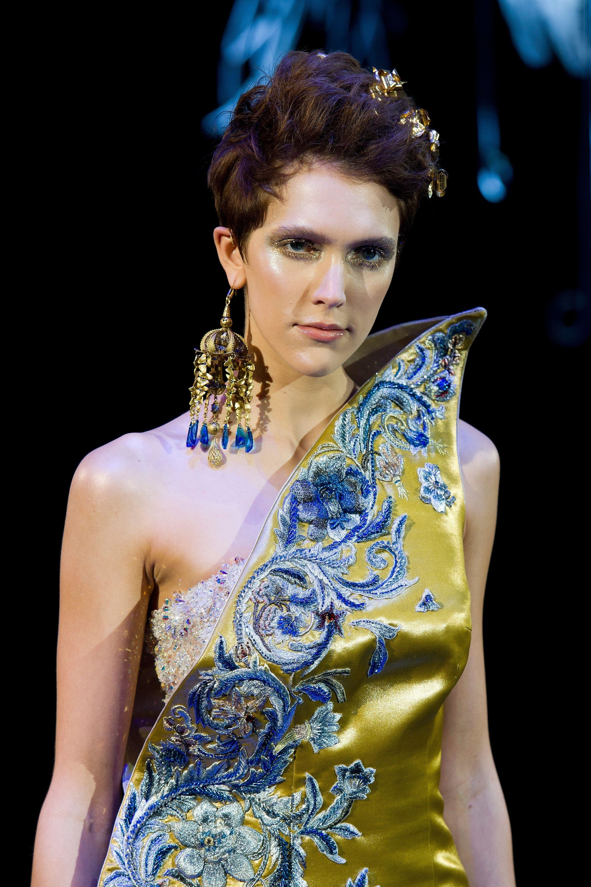 close up shot of model on the guo pei runway with golden hair accessories in her mane, wearing satin dress and statement earrings