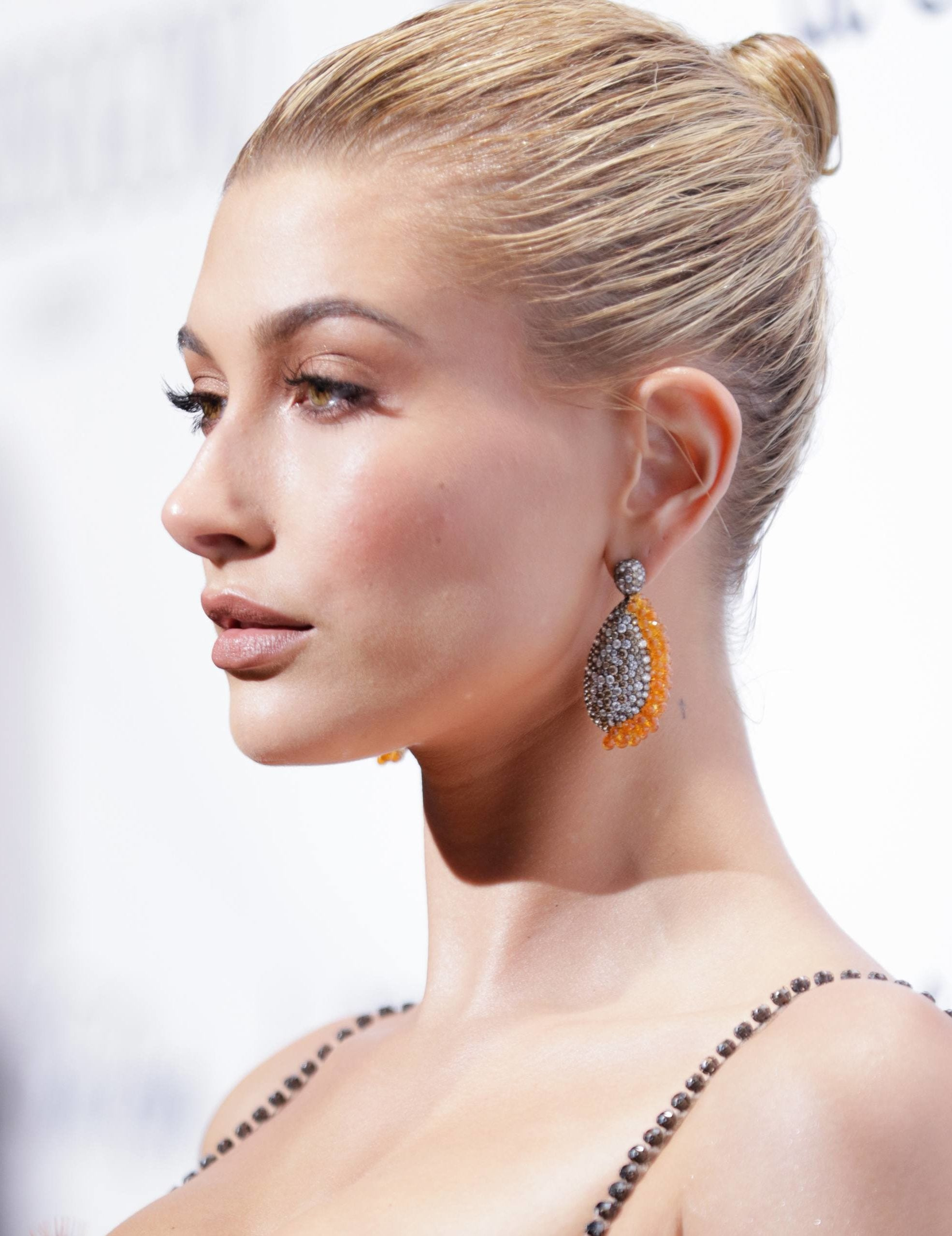 hailey baldwin with her blonde hair in a tight topknot style