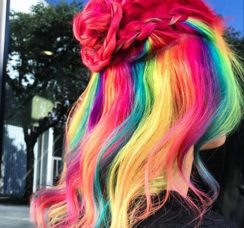 woman with froot loops inspired cereal hair styled into a half up braided bun at salon