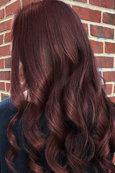 Red brown hair: Back shot of a woman with a wine red and brown long hair styled into loose curls.