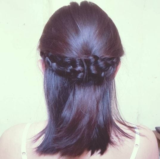 brunette with shoulder length hair in a half up braided crown style