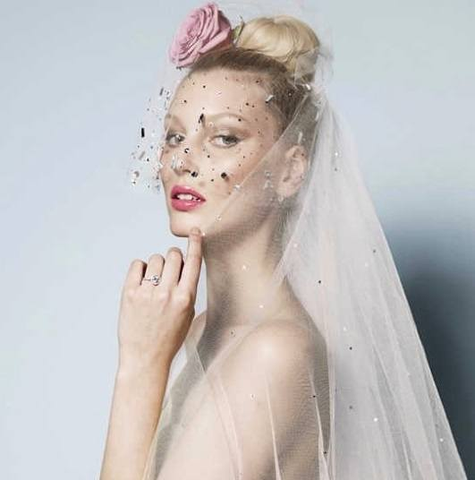 blonde bride with her hair in a high bun with a veil and pink flower hair accessory