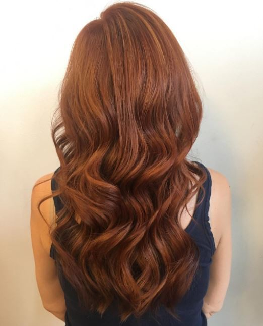 Red brown hair: Close up shot of woman with long auburn wavy hair.