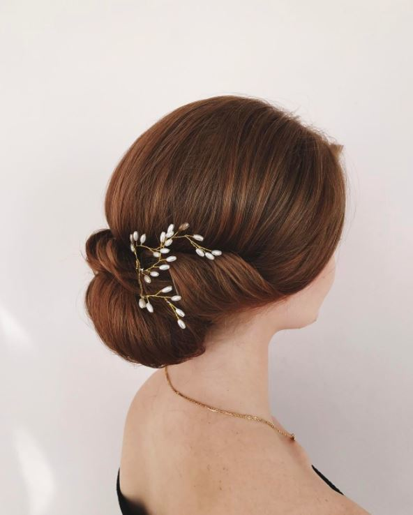 Red brown hair: Close up shot of a woman with chestnut brown hair with auburn highlights in it, styled into a floral chignon hairstyle