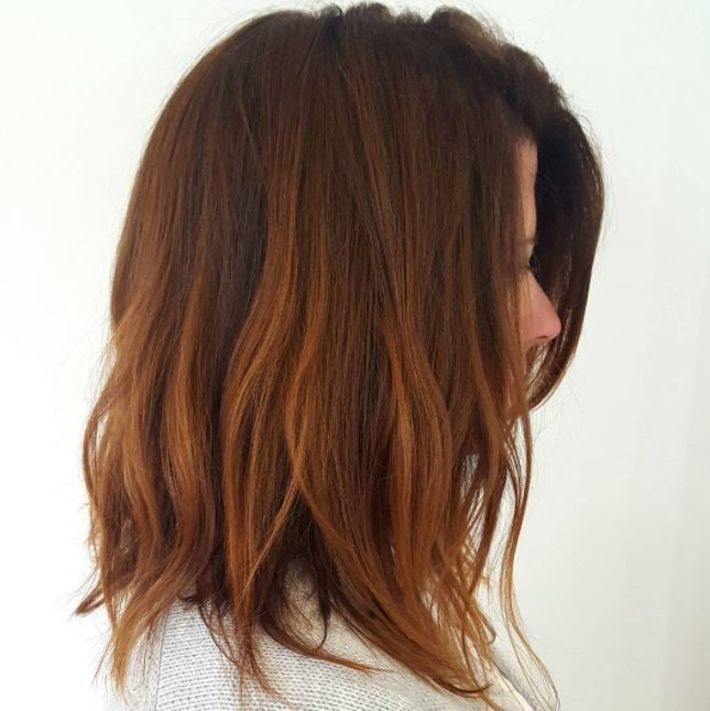 Red brown hair: Close up shot of a woman with cinnamon lob length tousled hair.