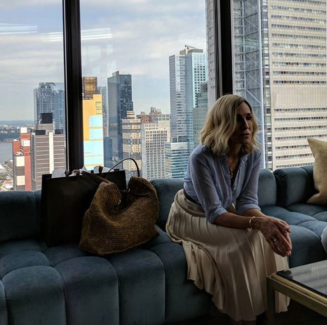 Sarah Jessica Parker sits on sofa with blonde wavy lob hairstyle