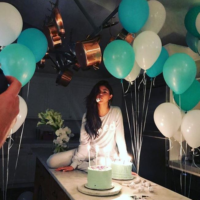 Selena Gomez - long dark brown wavy hair swept to one side surrounded by balloons