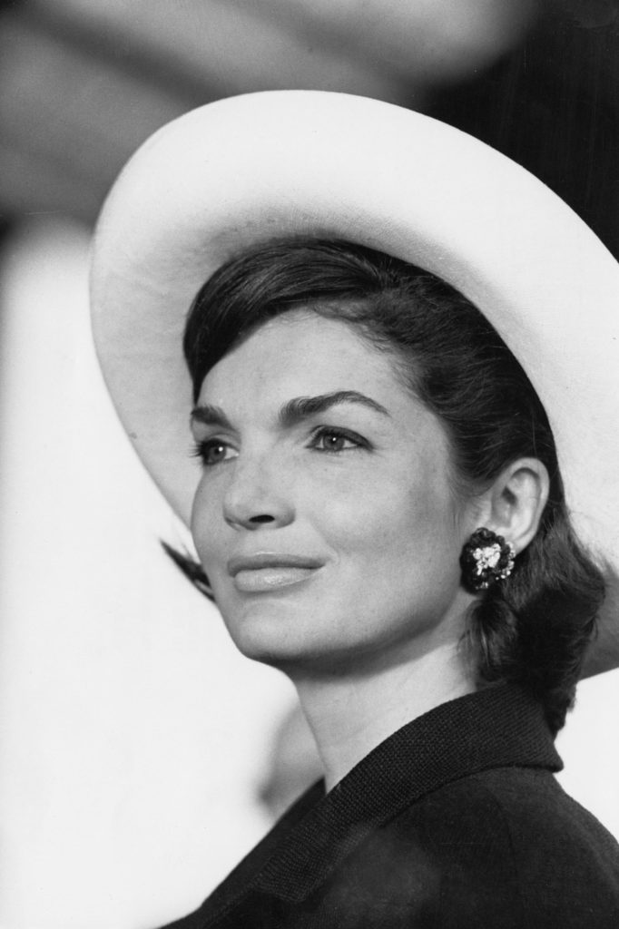 60s hairstyles: Jackie Kennedy shoulder length brown bob with flicked out ends wearing a white hat in black and white image