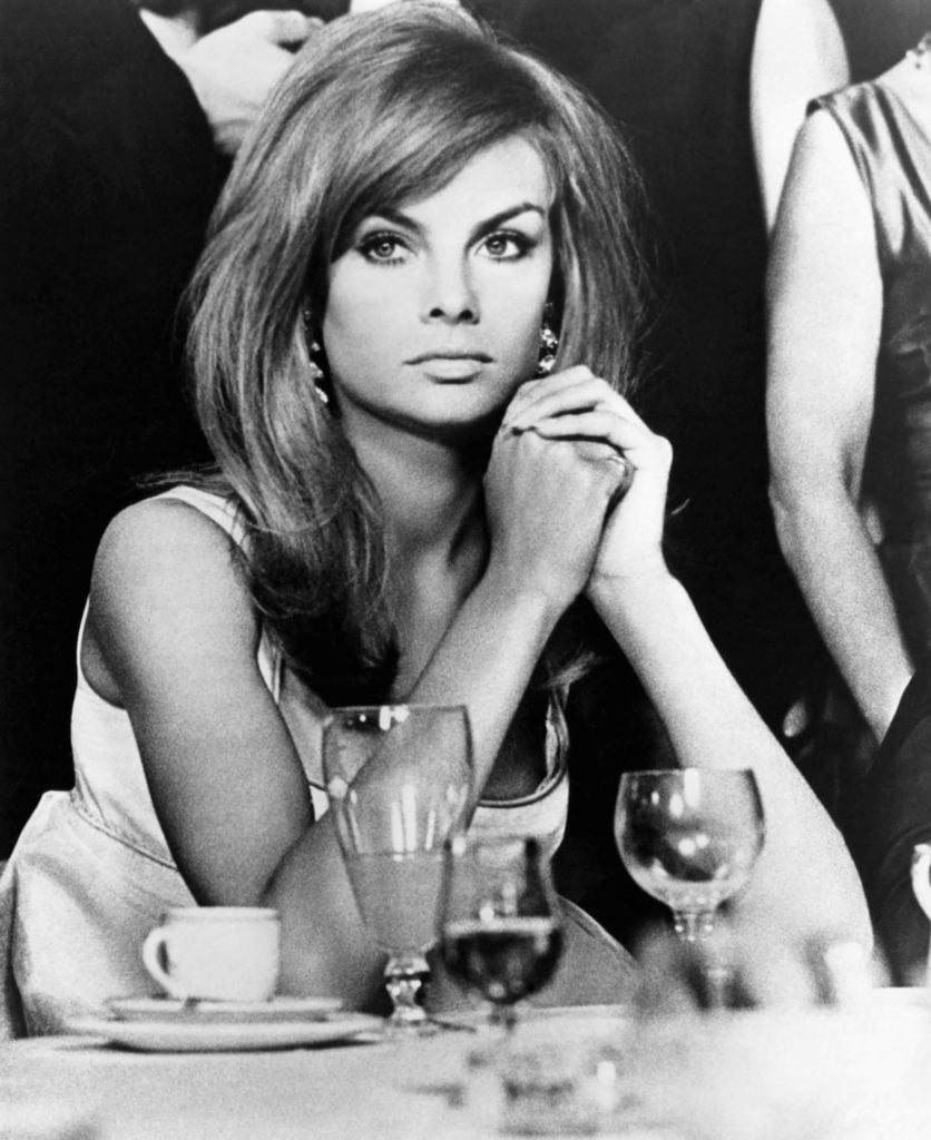 60s hairstyles: Jean Shrimpton in black and white image with brown medium length straight hair styled in a side parting with a sweeping side fringe