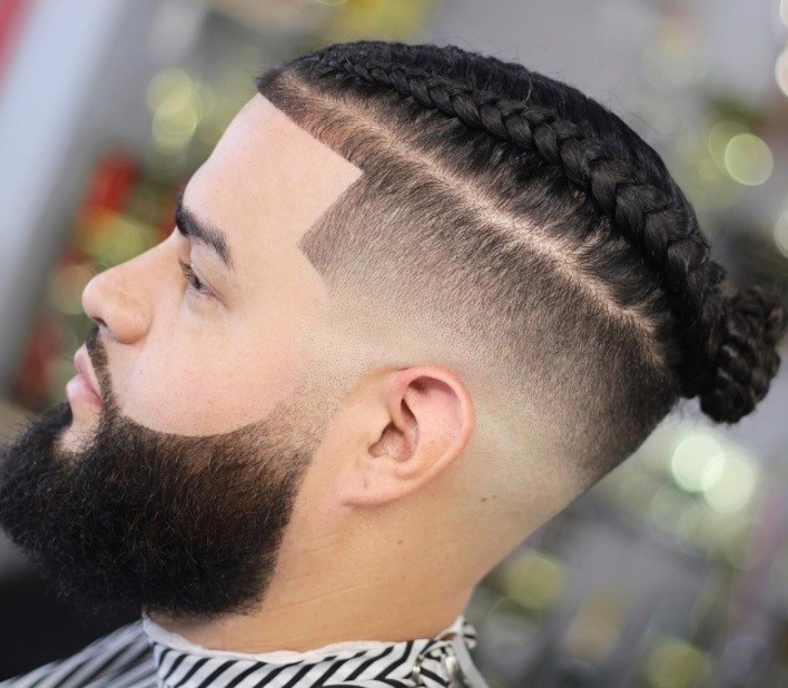 close up of a man with braided top knot men's hairstyle with undercut and beard at a salon