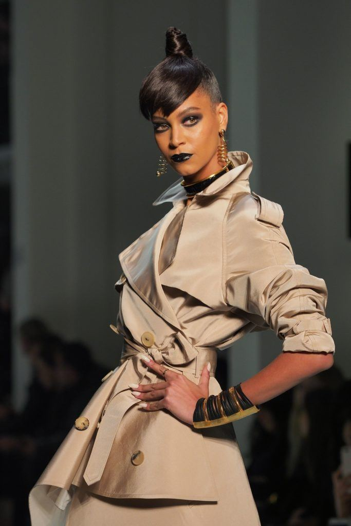 close up shot of model with high, sleek topknot with side part and undercut, wearing trench coat and posing on the jean paul gaultier paris haute couture ss18 runway