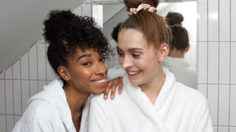 Leave-in conditioner: Shot of two girls in bathrobes, one with natural curly hair in a bun updo, the other with straight hair in a bun, too