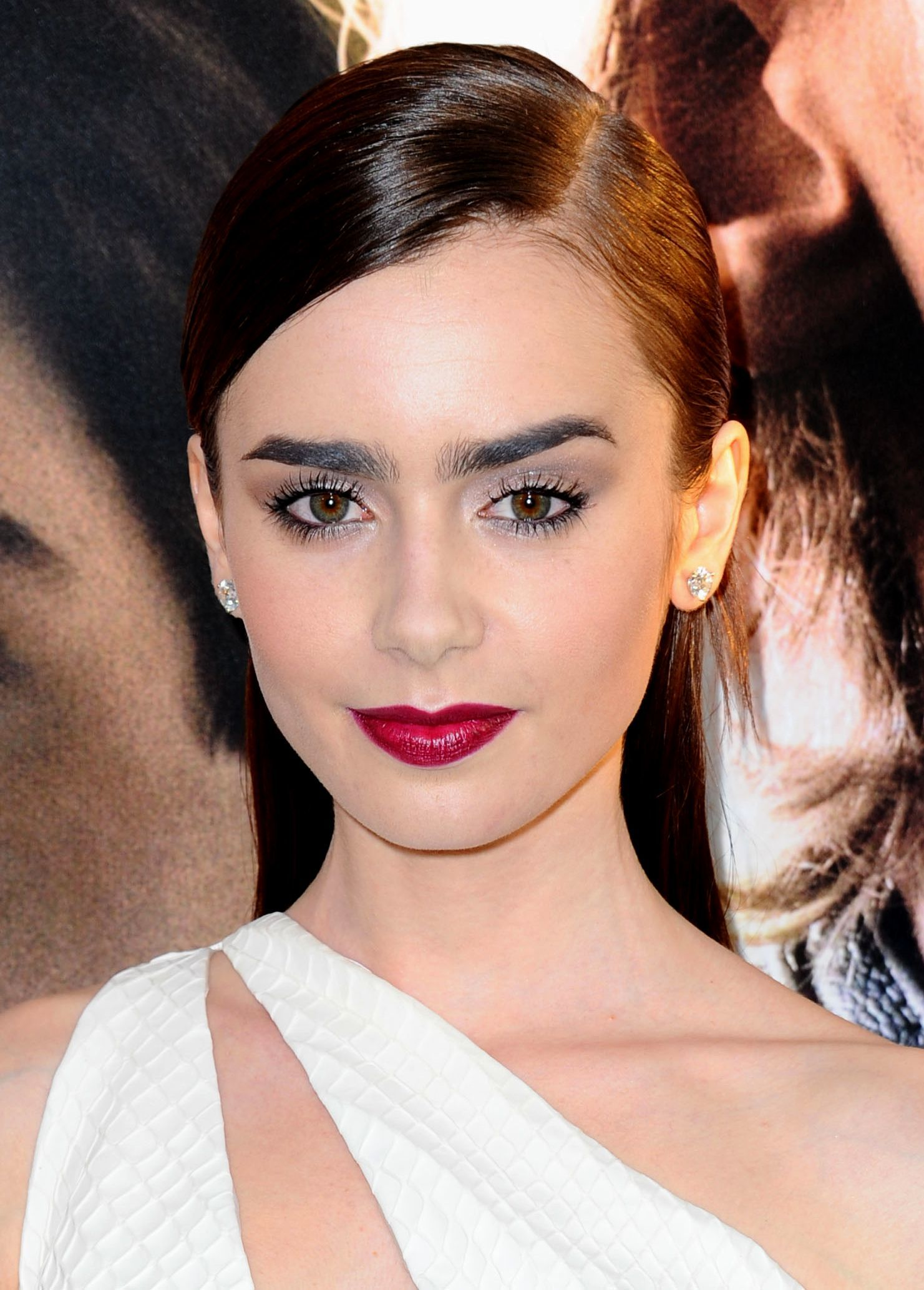 british american actress lily collins with her brunette long hair in a slick half up half down straight style