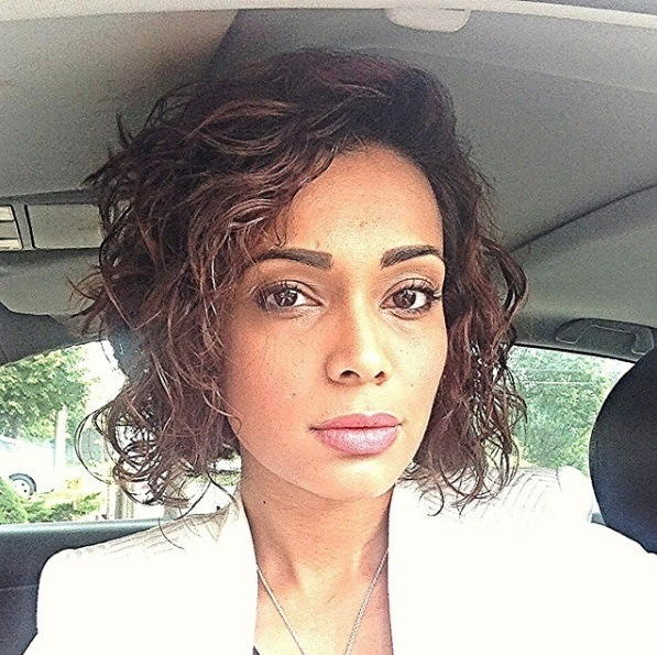 Car selfie of a woman with reddish brown hair in a long bob style curled with a wavy perm.