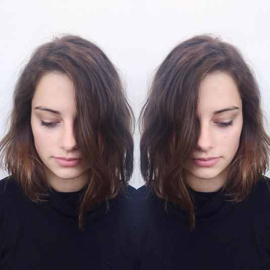 Double reflected photo of a woman with loosely permed bob length brunette hair with a side parting.