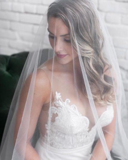 blonde bride with her hair in curls with a wedding veil covering her head