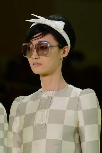 60s hairstyles: dark haired model on catwalk with hair in bouffant style with white ribbon headband