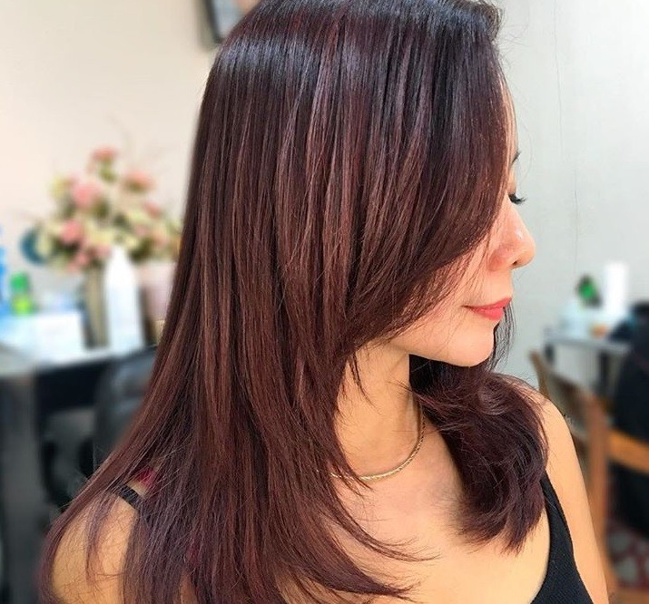 Red brown hair: Close up shot of a woman with shoulder-length medium mahogany hair with layers.