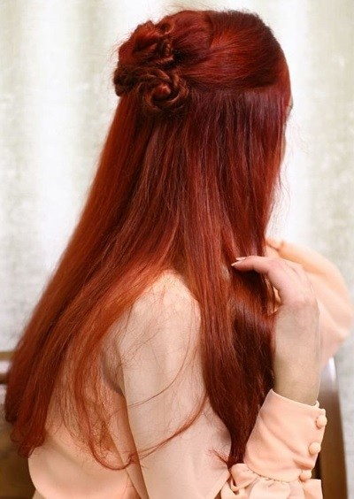 Game of Thrones hairstyles: Back view of a woman with long red hair in a half-up knotted bun hairstyle
