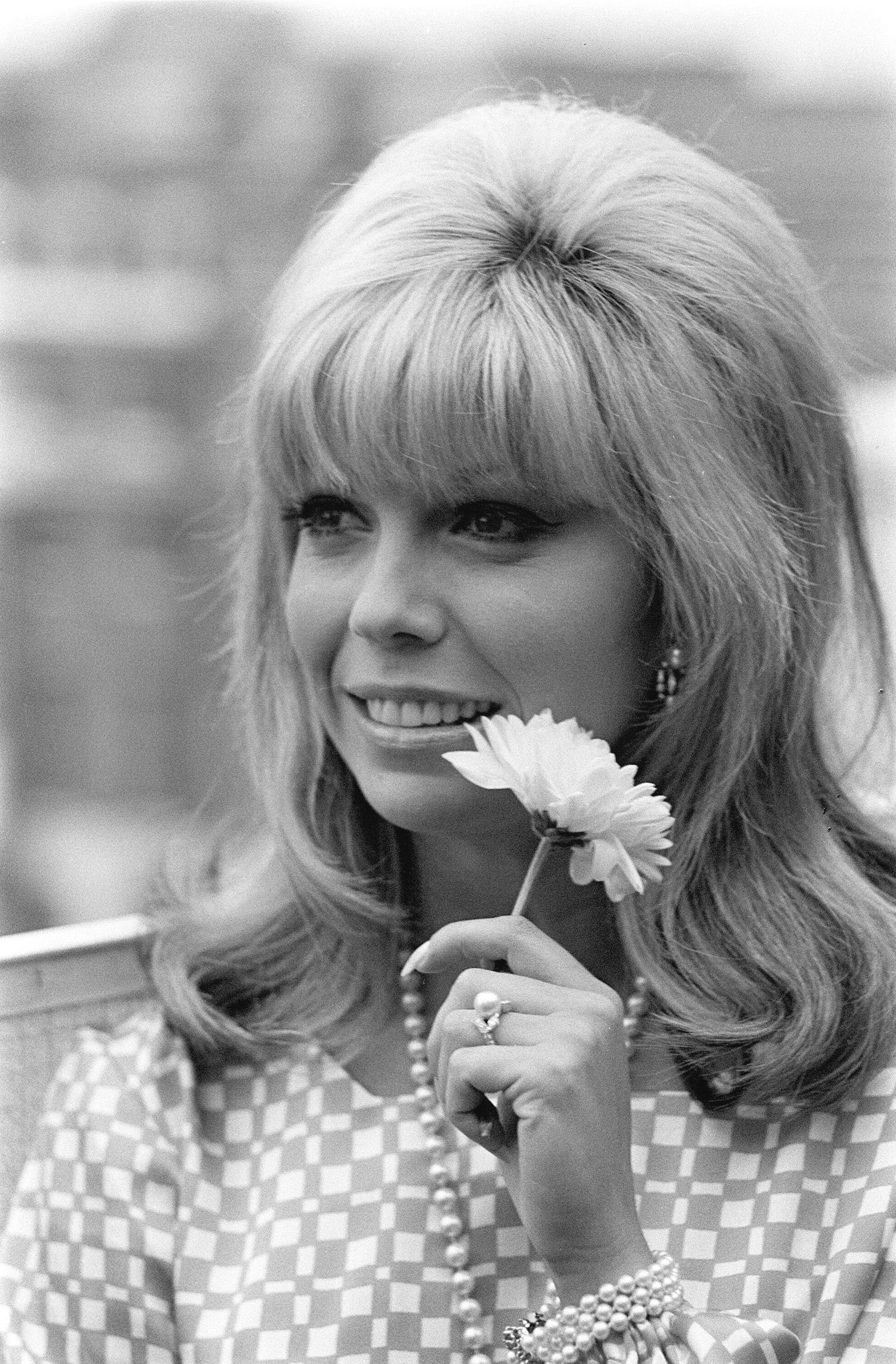 60s hairstyles: Nancy Sinatra with shoulder length blonde hair with backcombed roots, bangs and flicked out ends holding a flower in black and white image