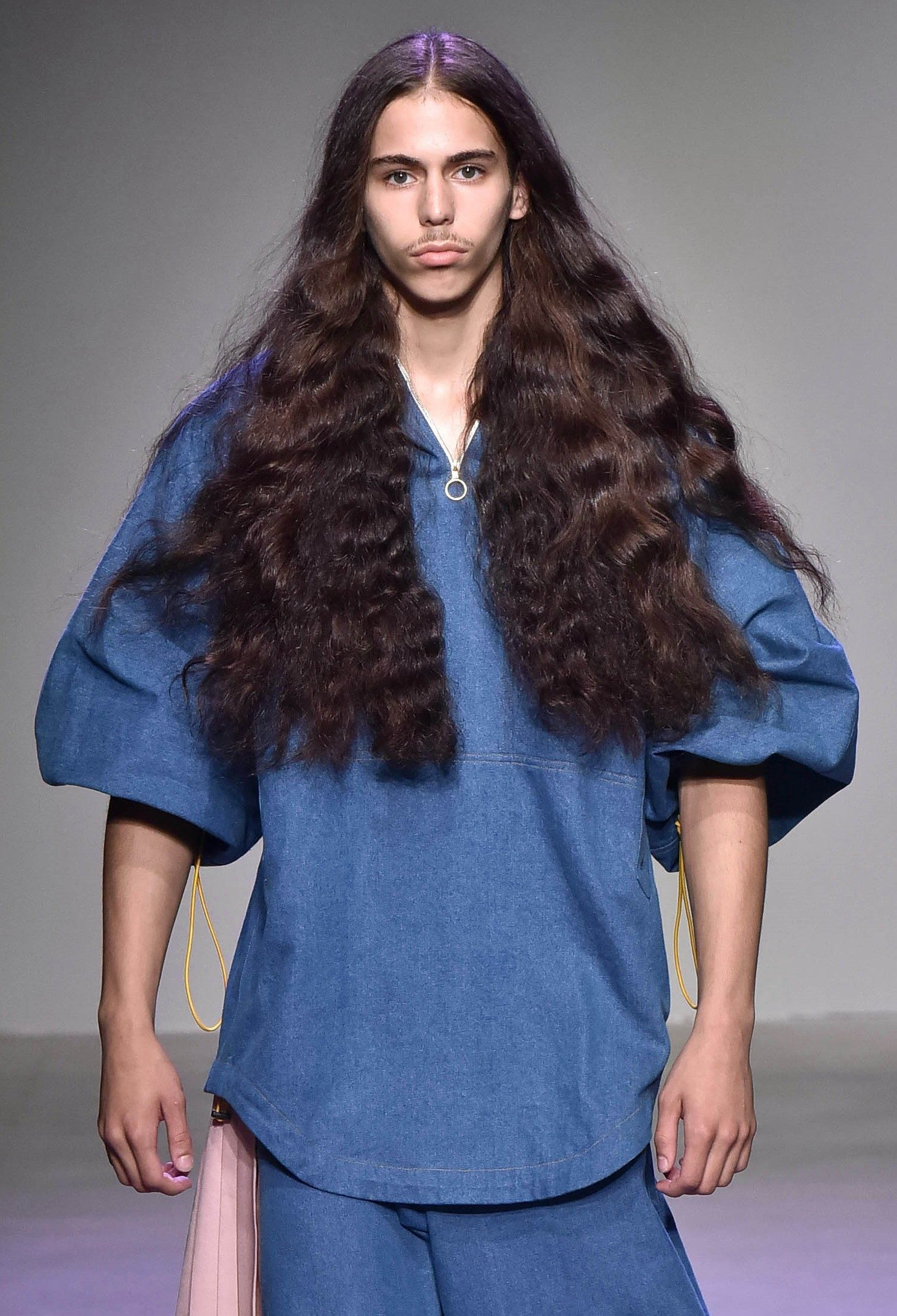 male model on the runway at the n p elliott nyfw mens show with chest length flowing wavy hair